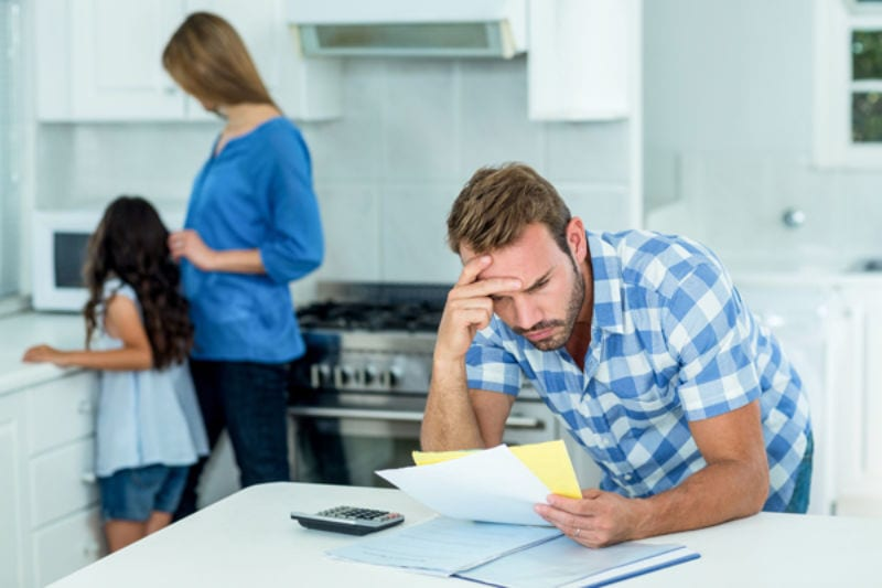 Worried father looking at bills with family in background